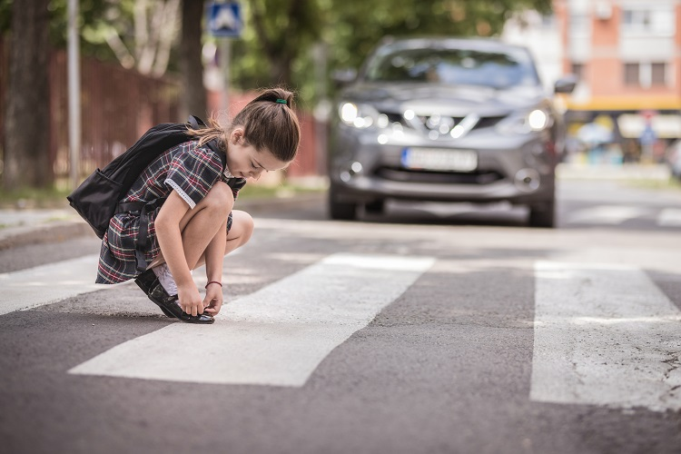 Girl fixing her shoes on at the crosswalk